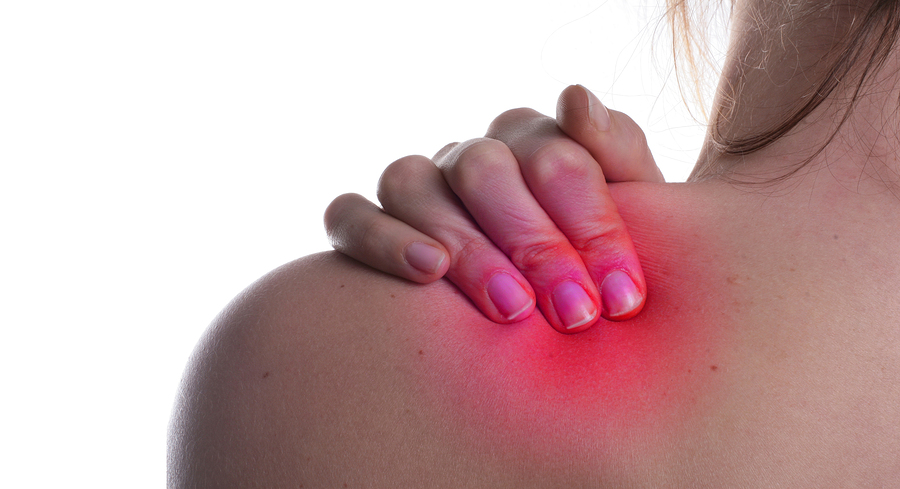 A woman hold her shoulder in pain. The area on the shoulder is higlighted to symbolize the pain.