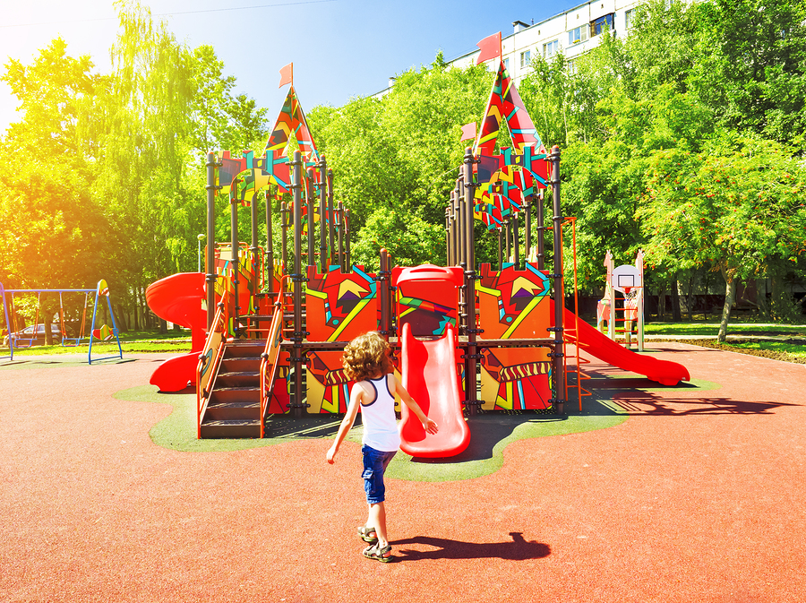The boy is having fun on the street playground. Swings and slides in the park for children. Children's playground bright colorful. A modern children's playground for children in the city park.